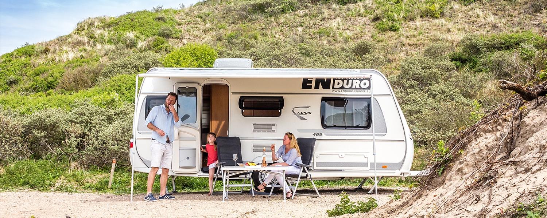 ENDURO Einbauservice Titelbild. Eine drei Köpfige Familie hält sich or einem Wohnwagen auf