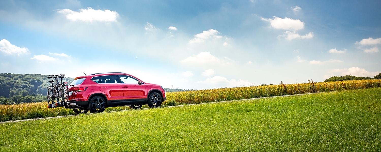 Ein rotes Auto mit Fahrradträger fährt durch eine Landschaft