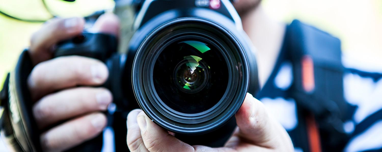 Montage- und Imagevideos Headerbild. Die Linse einer Kamera wird auf den Betrachter gerichtet