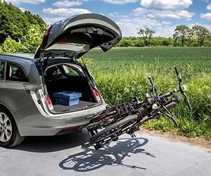 Auto mit geöffneten Kofferraum und abgekapptem Fahrradträger mit zwei Fahrrädern