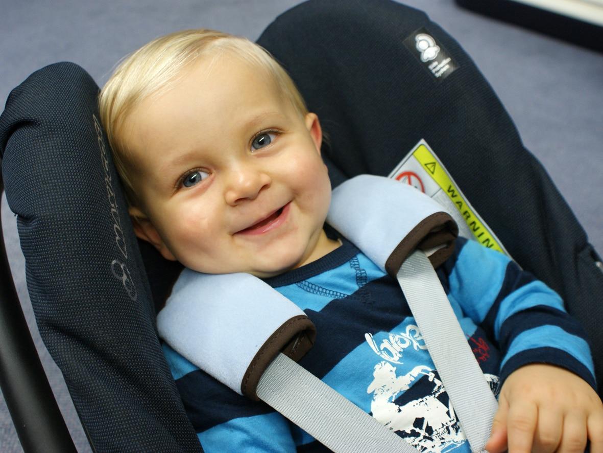 Ein Kleinkind im Kindersitz lächelt in die Kamera. Es hat Gurtpolster von Happy Kids Reisezubehör an seinen Kindersitzgurten.