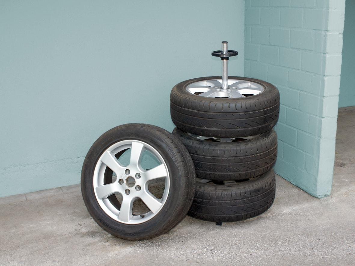 Ein Reifenbaum in einer Werkstatt oder Garage mit drei Reifen darauf, ein weiterer Reifen lehnt gegen die aufgestapelten Reifen.