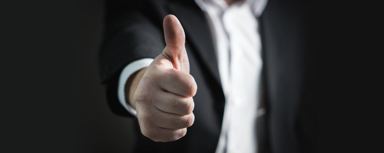Auszeichnungen und Testergebnisse Headerbild. Ein Mann im Anzug streckt seinen Daumen aus.
