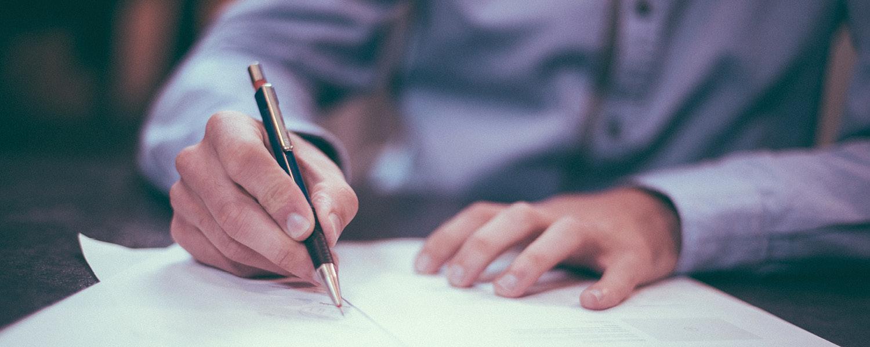 Karriere Headerbild. Eine Hand die einen Kugelschreiber hält und auf einem Papier unterschreibt.