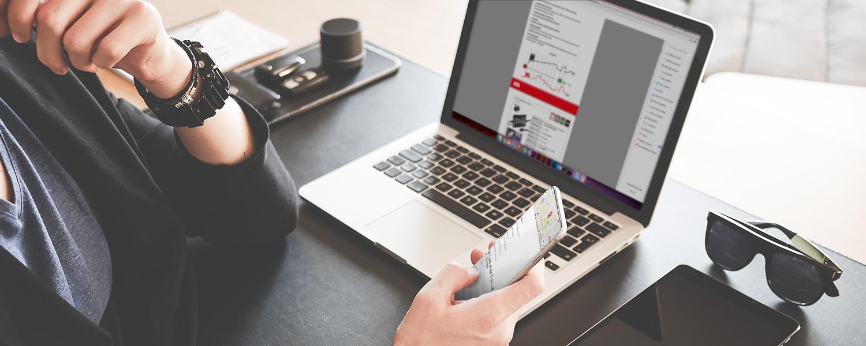 Frau am Schreibtisch schaut auf Ihr Handy. Der Bildschirm zeigt den Download Bereich der Webseite.
