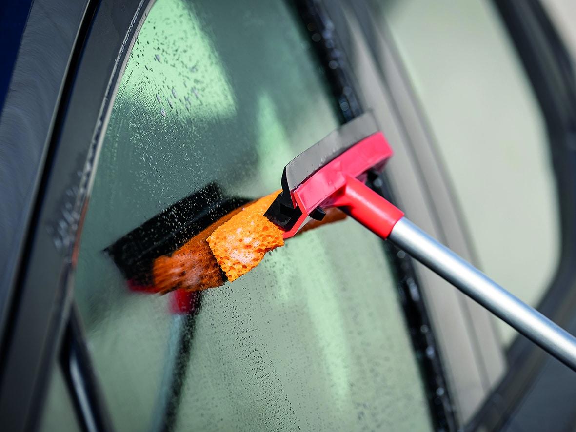 Ein Scheibenwascher wischt über eine nasse Autoscheibe.