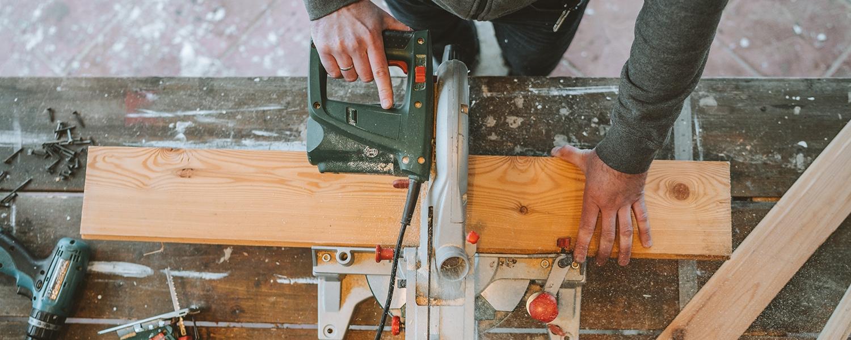 Ballistol Produktvideos Headerbild. Vogelperspektive auf eine Werkbank, ein Holzbrett wird mit einer Kreissäge geschnitten.
