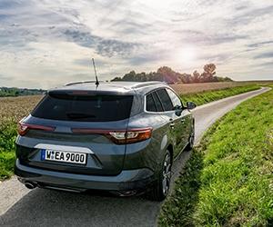 Ein graues Auto mit getönten Scheiben fährt durch eine grüne Landschaft.